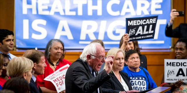 Sen. Bernie Sanders, I-Vt., center, accompanied by Sen. Kirsten Gillibrand, D-N.Y., center right, speaks at a news conference on Capitol Hill in Washington, Wednesday, Sept. 13, 2017, to unveil their Medicare for All legislation to reform health care. (AP Photo/Andrew Harnik)