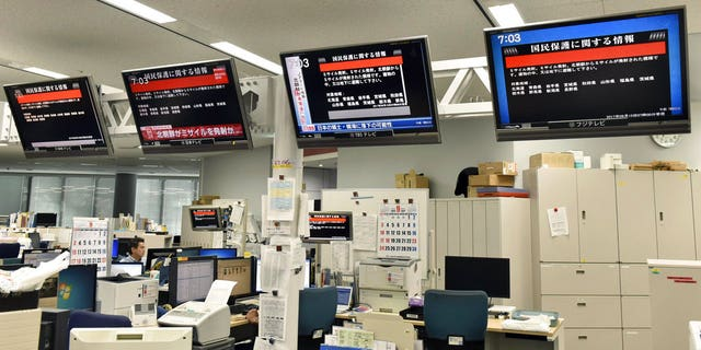 "TV monitors in Tokyo, Japn show the ""J-alert"" warning siren after North Korea's missile launch."