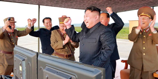 In this undated photo provided by the North Korean government, leader Kim Jong Un celebrates what is said to be the first successful test launch of an intermediate rang Hwasong-12 missile.