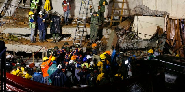 Rescue personnel work on the rescue of a trapped child at the collapsed Enrique Rebsamen primary schoool in Mexico City.