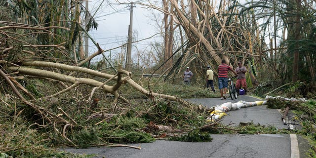 Locals help clear debris from a road after the passing of Hurricane Maria, in Yabucoa, Puerto Rico.