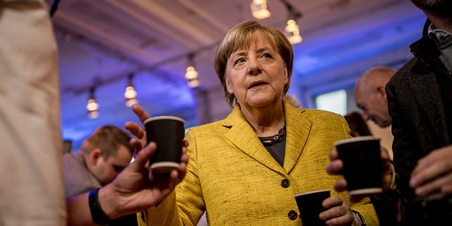 German chancellor Angela Merkel gets a cup of coffee during an event with election campaign workers in Berlin, Saturday, Sept. 23, 2017 ahead of Germany's election on Sunday. (Michael Kappeler/dpa via AP)