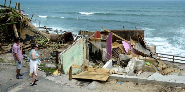 People walk by building that was destroyed in the community La Perla in Old San Juan during Hurricane Maria in San Juan, Puerto Rico, Monday, Sept. 25, 2017.