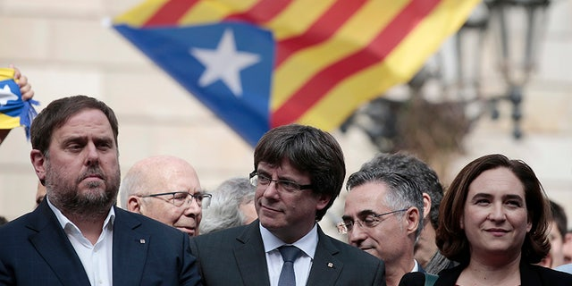 "Catalan President Carles Puigdemont (center) says the region is set to declare its independence from Spain ""in a matter of days."""