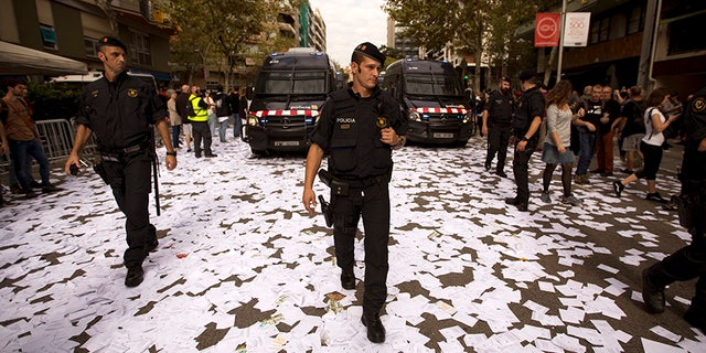 Catalan Mossos d'Esquadra officers walk a long a street covered with referendum ballots thrown by pro-independence demonstrators, during a rally in front of the Spanish Partido Popular ruling party headquarters in Barcelona, Spain, Tuesday Oct. 3, 2017. Labor unions and grassroots pro-independence groups are urging workers to hold partial or full-day strikes throughout Catalonia to protest alleged brutality by police during a referendum on the region's secession from Spain that left hundreds of people injured. (AP Photo/Emilio Morenatti)