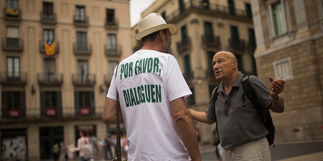 "A man, wearing a t-shirt reading in Spanish: ""Please, talk"" chats with a passer-by about the current political situation in Catalonia, in Barcelona, Friday, Oct. 6, 2017"