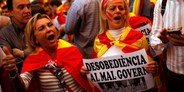 "Demonstrators shout slogans, some of them holding a banner reading in Catalan ""disobedience to the bad government"", as they gather near a headquarters of federal police in Barcelona."