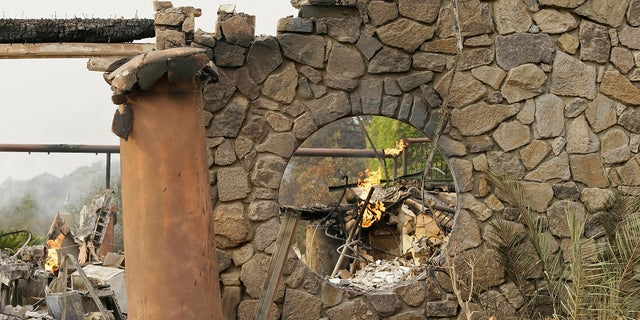 Flames continue to smolder at the Signorello Estate winery Tuesday.