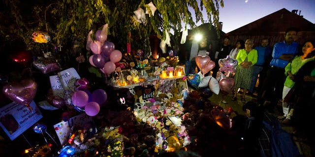People gather at a memorial for Sherin Mathews at a tree behind her home.
