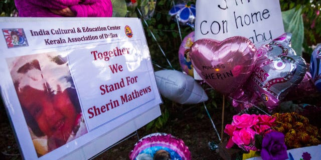 Photo, signs, flowers and other items are gathered at a memorial for Sherin Mathews.