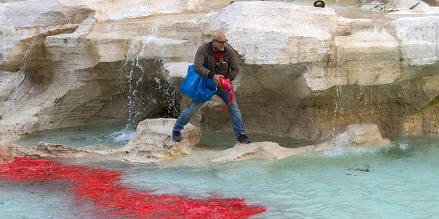 Graziano Cecchini pours red paint in the water of the Trevi Fountain, in Rome, Italy, Thursday,  Oct. 26, 2017. A self-proclaimed artist, Cecchini repeated the same act that stunned the world 10 years ago, on Oct. 19, 2007. (Massimo Percossi/ANSA via AP)
