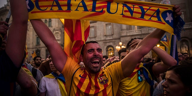 Pro-independence demonstrators cheer outside the Catalan parliament, in Barcelona, Oct. 27, 2017.