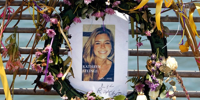 This July 17, 2015, file photo shows flowers and a portrait of Kate Steinle displayed at a memorial site on Pier 14 in San Francisco, Calif. The bullet that killed Kate Steinle ago ricocheted off the ground about 100 yards away before hitting her in the back and later launching a criminal case at the center of a national immigration debate.