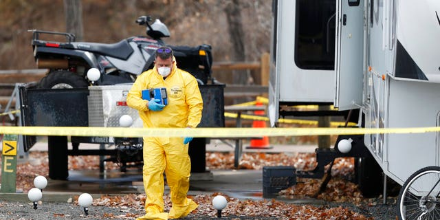 An investigator emerges with evidence from a trailer in a park along Clear Creek in which the body of a 63-year-old man was found Tuesday.