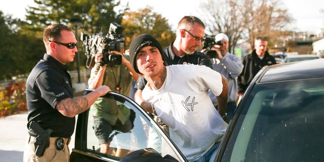 Austin Boutain, a suspect in Monday night's fatal shooting of University of Utah student ChenWei Guo, is led out of the University of Utah Department of Public Safety in Salt Lake City on Tuesday.
