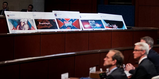 Facebook ads linked to a Russian effort to disrupt the American political process are displayed as, from left, Google's Senior Vice President and General Counsel Kent Walker, Facebook's General Counsel Colin Stretch, and Twitter's Acting General Counsel Sean Edgett, testify during a House Intelligence Committee hearing.