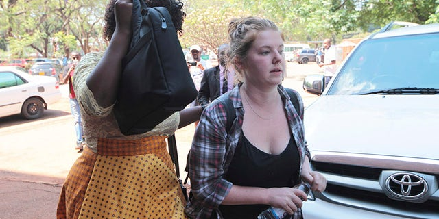 Martha O' Donovan, right, appears at the Harare Magistrates court escorted by a plain clothes police officer shielding her face in Harare.