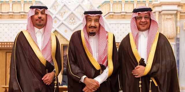 In this photo provided by the Saudi Press Agency, the new Economy and Planning Minister, Mohammad al-Tuwaijri, right and the new National Guard chief, Prince Khalid bin Ayyaf al-Muqrin, left, pose for a photo with King Salman during a swearing in ceremony in Riyadh.