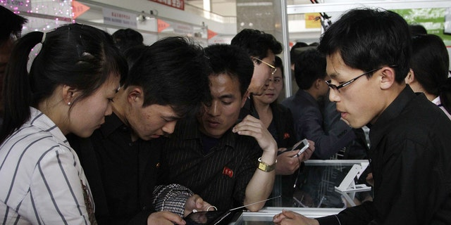 In this May 15, 2013, file photo, North Koreans take a look at the Samjiyon tablet computer produced for the North Korean market for sale at the 16th Pyongyang Spring International Trade Fair in Pyongyang.