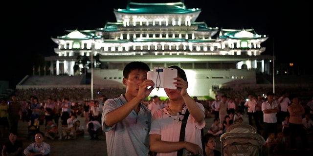In this Sunday, July 27, 2014, file photo, a North Korean couple use a smartphone to photograph fireworks in at Kim Il Sung Square in Pyongyang, North Korea.