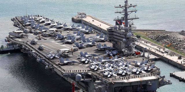 USS Ronald Reagan (CVN 76) is escorted into Busan port, South Korea, after completing a joint drill with the South Korean military.