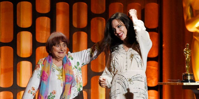 French director Agnes Varda, left, celebrates onstage with her honorary Oscar as presenter Angelina Jolie looks on at the 2017 Governors Awards at The Ray Dolby Ballroom