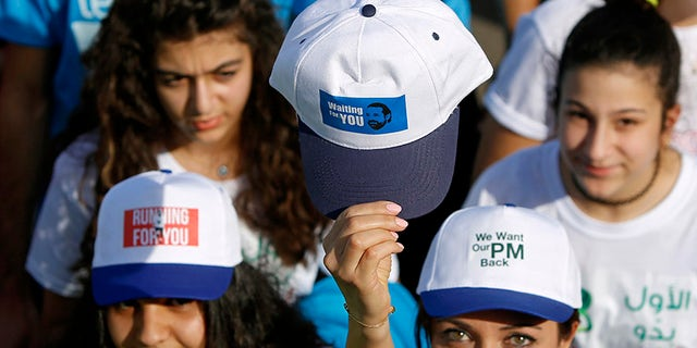 Runners and spectators at the 15th annual Beirut marathon wore hats and held signs in support of Lebanese PM Saad Hariri.