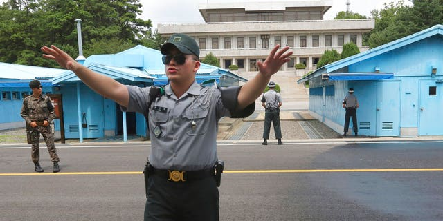 A South Korea army soldier gestures at the border villages of Panmunjom in Paju, South Korea.