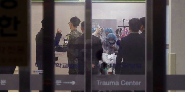 A South Korean army soldier, second from left, is seen as medical members treat an unidentified injured person, believed to be a North Korean soldier, at a hospital in Suwon, South Korea, Monday.