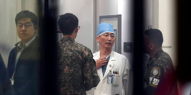 Doctors talk while treating a patient, believed to be a North Korean soldier, at a hospital in Suwon, South Korea.