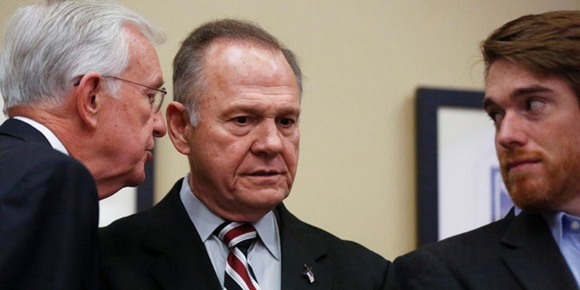 Former Alabama Chief Justice and U.S. Senate candidate Roy Moore listens as a campaign member talks to him before Moore speaks at the Vestavia Hills Public library on Saturday.