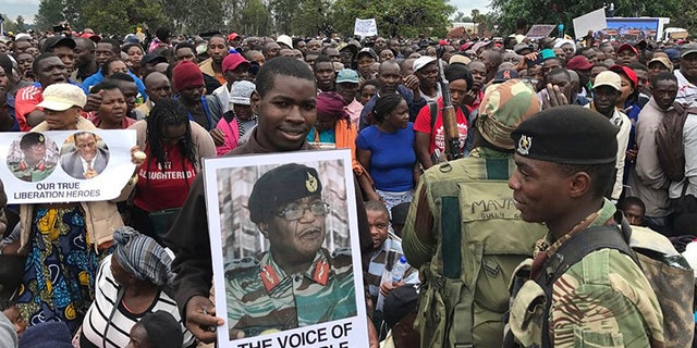 People gather to demonstrate for the ouster of 93-year-old President Robert Mugabe who is virtually powerless and deserted by most of his allies, in Harare, Zimbabwe.