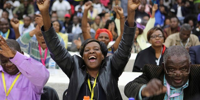 Members of the Zanu pf Central committee react after the ruling party fired President Robert Mugabe, in Harare, Sunday.