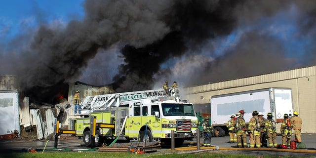 Firefighters try to control a blaze at a cosmetics plant in New York on Monday.