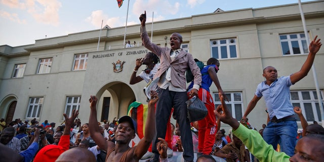 Zimbabweans celebrate outside the parliament building immediately after hearing the news that President Robert Mugabe had resigned, in downtown Harare, Zimbabwe Tuesday, Nov. 21, 2017. Mugabe resigned as president with immediate effect Tuesday after 37 years in power, shortly after parliament began impeachment proceedings against him.