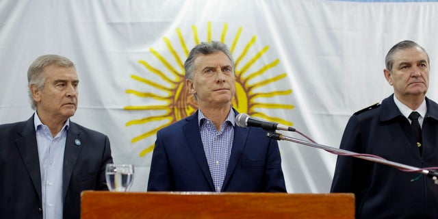 Argentine President Mauricio Macri, pauses as he gives a statement, flanked by Defense Minister Oscar Aguad, left, and Chief of the General Staff of the Navy Marcelo Eduardo Hipolito Srur at the navy headquarters in Buenos Aires, Argentina, Friday, Nov. 24, 2017. Macri said the international search for a submarine carrying 44 crew members that has been lost in the South Atlantic since Nov. 15 will continue and that the sub's disappearance will be investigated.