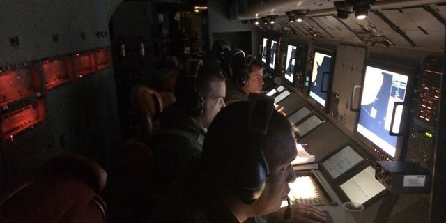 In this Thursday, Nov. 23, 2017 photo provided by Brazil's Air Force, Brazilian military aid in the search for Argentina's missing submarine as they fly on a mission over the South Atlantic, after leaving a base in Bahia Blanca, Argentina.