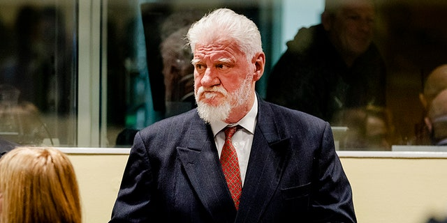 """A court guard has told reporters Slobodan Praljak, 72, was alive and """"receiving medical attention"""" after apparently taking poison in court."""