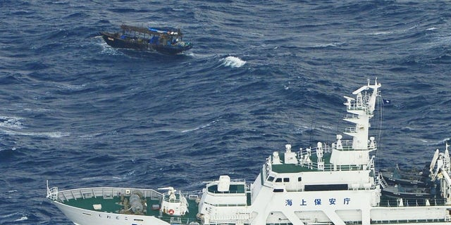 The Japanese Coast Guard approached the drifting wooden boat Wednesday to inspect it and the North Korean men aboard.