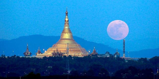 The moon rises behind the mountain range seen from Naypyitaw, Burma, on Sunday.