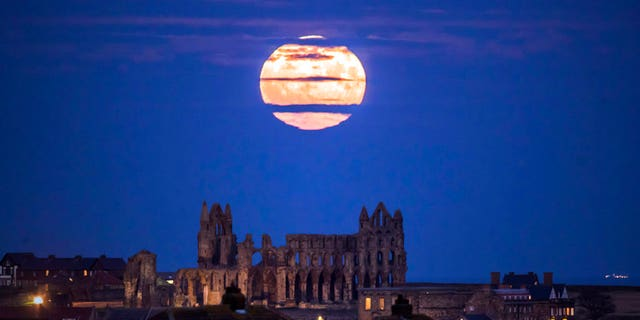 The supermoon rises above Whitby Abbey in Whitby, northeast England, on Sunday.