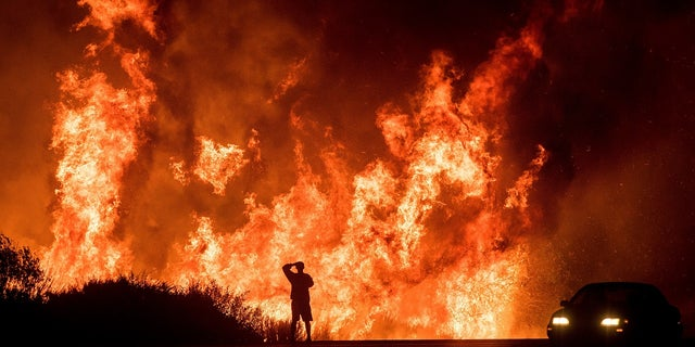 A man watches the massive flames burning in a Southern California neighborhood.