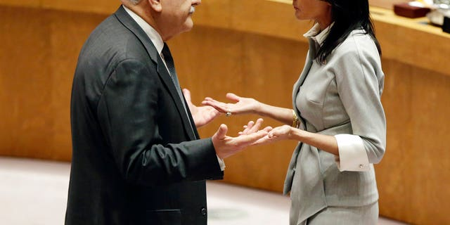 Palestinian Ambassador to the United Nations Riyad Mansour, left, and U. S. Ambassador Nikki Haley confer before a Security Council meeting at United Nations headquarters, Friday, Dec. 8, 2017.