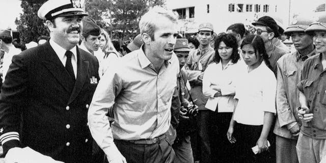 U.S. Navy Lt. Cmdr. John McCain, center, is escorted by Lt. Cmdr. Jay Coupe Jr., to Hanoi, Vietnam's Gia Lam Airport, after McCain was released from captivity.