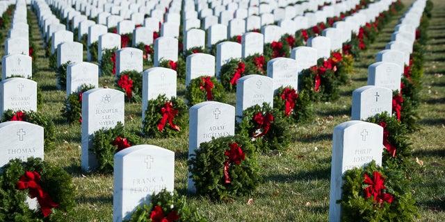 Wreaths rest against headstones at Arlington National Cemetery as Wreaths Across America places remembrance wreaths on headstones at the cemetery in Arlington, Va., Saturday, Dec. 16, 2017.