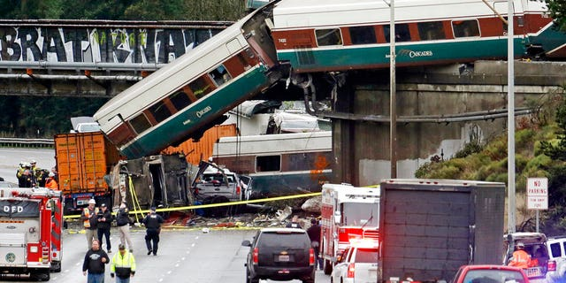 Several train cars fell over the overpass and onto Interstate 5 in Washington state on Monday.