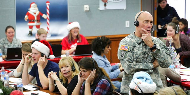 NORAD and USNORTHCOM Chief of Staff Maj. Gen. Charles D. Luckey joins other volunteers taking phone calls from children around the world asking where Santa is inside a phone-in center during the annual NORAD Tracks Santa Operation, at the North American Aerospace Defense Command, at Peterson Air Force Base, Colo.
