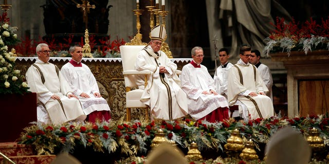 Pope Francis, background center, celebrates the Christmas Eve Mass in St. Peter's Basilica at the Vatican.