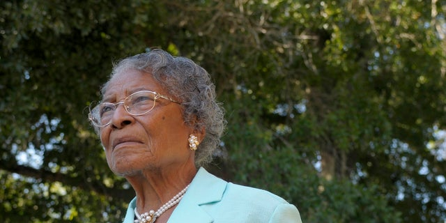Recy Taylor, then 90, holds a photo of herself from her days in Abbeville, Ala., outside her home in Winter Haven, Fla.