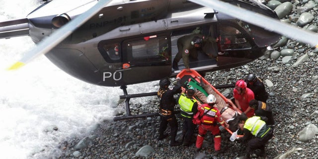 Rescue workers load an injured man on a stretcher after he was retrieved from the bus.